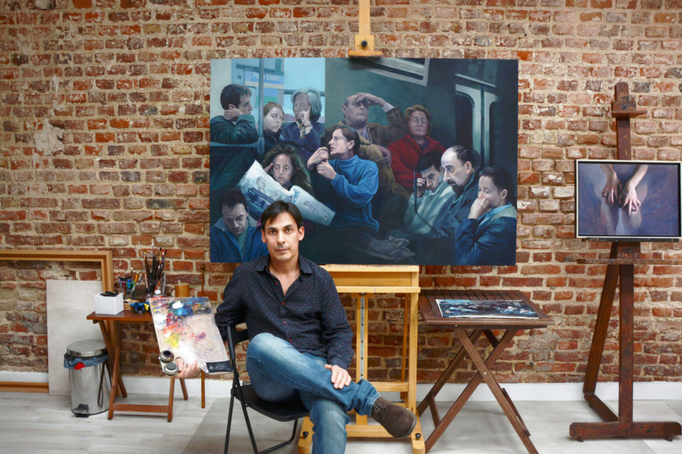"""Cristian Avilés in his Spanish studio. In the back his last paintng """"People in Subway"""". Photo by Jose Antonio Ramirez"""