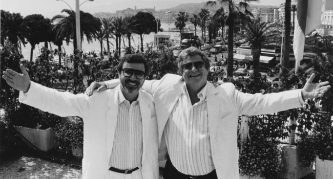 Israel film producers and directors Yoram Globus (left) and Menahem Golan, owners of Cannon Films, at the Cannes Film Festival, France, circa 1987. (Photo by Richard Blanshard/Getty Images)